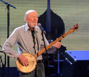 FILE- In this Sept. 21, 2013 file photo, Pete Seeger performs on stage during the Farm Aid 2013 concert at Saratoga Performing Arts Center in Saratoga Springs, N.Y.  Organizers say the New York music festival Clearwater's Great Hudson River Revival, founded by the late folk legend Pete Seeger, will return to the village of Croton -on-Hudson, New York, on June 17-18, 2017. (AP Photo/Hans Pennink, File)