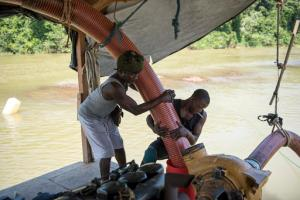 In this Oct. 30, 2016 photo, two men, both indigenous Paramaka, known as Rasta, left, and Luck, right, independent miners working on a gold pontoon on the Marowijne river near the town of Langa Tabiki set up a mining opetation. The hose they mounting is used to suck up mud from the river bottom. They say they are able to find much less gold in the river than on land. Many independent miners have left the area, leaving Langa Tabiki a ghost town. (AP Photo/Pieter Van Maele)