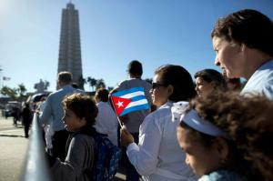 Mourners line up at Revolution Plaza, the site of two days of tributes to the late Fidel Castro, in Havana, Cuba, Monday, Nov. 28, 2016. Thousands of Cubans began lining up early carrying portraits of Fidel Castro, flowers and Cuban flags for the start of week-long services bidding farewell to the man who ruled the country for nearly half a century. (AP Photo/Natacha Pisarenko)