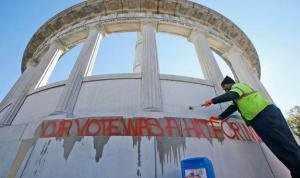 "City workers prepare to clean graffiti from the statue of Confederate President Jefferson Davis in Richmond, Va., Thursday, Nov. 10, 2016. The graffiti reads ""Your Vote Was A Hate Crime."" (AP Photo/Steve Helber)"