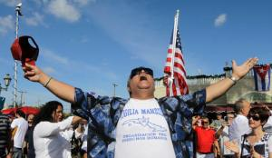 A member of the Cuban community celebrates the death of Fidel Castro, Saturday, Nov. 26, 2016, in the Little Havana area in Miami. Castro, who led a rebel army to improbable victory in Cuba, embraced Soviet-style communism and defied the power of 10 U.S. presidents during his half century rule, died at age 90. (AP Photo/Alan Diaz)