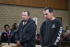Theo Jackson, left, and Willem Oosthuizen, right, appear in the Magistrates Court in Middelburg, South Africa Wednesday, Nov. 16, 2016. Two white South Africans accused of forcing a black man into a coffin and threatening to set him on fire appeared before a judge on Wednesday as demonstrators protested against racism outside the courthouse. (AP Photo)