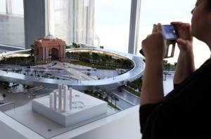 A woman takes a photograph of a model of the Hyperloop One project during a news conference in Dubai, United Arab Emirates, Tuesday, Nov. 8, 2016. The futuristic city-state of Dubai announced a deal on Tuesday with Los Angeles-based Hyperloop One to study the potential for building a line linking it to the Emirati capital of Abu Dhabi. (AP Photo/Jon Gambrell)