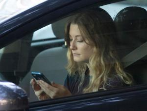 FILE - In this Wednesday, June 22, 2016, file photo, a driver uses her mobile phone while sitting in traffic in Sacramento, Calif. The government wants smartphone makers to lock out most apps when the phone is being used by someone driving a car. The voluntary guidelines unveiled Wednesday, Nov. 23, 2016, are designed to reduce crashes caused by drivers distracted by phones. (AP Photo/Rich Pedroncelli, File)