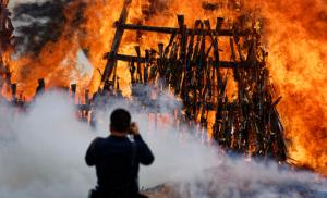 A photographer takes pictures of a pile of 5,250 illegal weapons as they are burned by Kenyan police in Ngong, near Nairobi, in Kenya Tuesday, Nov. 15, 2016. The weapons consisted of both confiscated and surrendered firearms that had been stockpiled over almost a decade and were destroyed by police as a message to the public to surrender others. (AP Photo/Ben Curtis)
