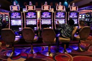 FILE - In this Oct. 3, 2014, file photo, a visitor to the Resorts World Casino at the Aqueduct racetrack plays an electronic slot machine, in the Queens borough of New York. The casino said on Nov. 3, 2016, that a woman who was shown that she won nearly $43 million on a penny slot in August 2016 actually won $2.25. (AP Photo/Julie Jacobson, File)