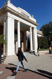 In this Nov. 21, 2016 photograph, a student walks across the University of Southern Mississippi campus in Hattiesburg, Miss. The University of Southern Mississippi is the latest public university to cut tuition across the board for out-of-state students. (AP Photo/Rogelio V. Solis)