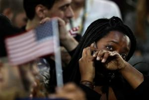 FILE - In this Nov. 8, 2016 file photo, a woman weeps as election results are reported during Democratic presidential nominee Hillary Clinton's election night rally in the Jacob Javits Center glass enclosed lobby in New York.  As Donald Trump approaches his inauguration as president, young Americans have a deeply pessimistic view about his incoming administration, with young blacks, Latinos and Asian Americans particularly concerned about what's to come in the next four years.  (AP Photo/Frank Franklin II)