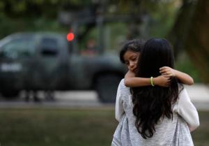 A woman carries her child near a military truck, after soldiers evacuated Plaza Las Americas mall following gunfire in Cancun, Mexico, Tuesday, Jan. 17, 2017. Gunmen attacked the state prosecutor's office in this Caribbean resort city Tuesday, ratcheting up tensions just a day after a deadly shooting at a music festival in a nearby town. (AP Photo/Rebecca Blackwell)