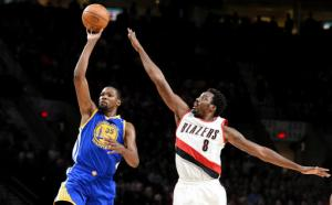 Golden State Warriors forward Kevin Durant puts up a shot on Portland Trail Blazers forward Al-Farouq Aminu during the first half of an NBA basketball game in Portland, Ore., Sunday, Jan. 29, 2017. (AP Photo/Steve Dykes)