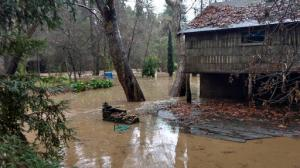 Flooded properties are seen in Paradise Park in Santa Cruz County, Calif., Sunday morning, Jan. 22, 2017. Fast-moving floodwaters swept through mountain communities and residents fled homes below hillsides scarred by wildfires as the third and largest in the latest series of storms brought powerful rain Sunday and warnings about damaging mudslides. (Ryan Masters/The Santa Cruz Sentinel via AP)