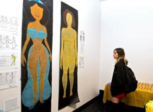 "In this Friday, Dec. 9, 2016, photo, Sam Lane looks at the artwork ""Female Figures"" prior to the Animated Women symposium at California Institute of the Arts, in Valencia, Calif. The California Institute of the Arts was created partly by Walt Disney's desire to bring more top-flight animators into the profession. And it has during its 47 years, though for a long time almost all were men. Now, nearly three-quarters of CalArts' more than 250 animation students are women, and there's a new goal: Ensure that when they land jobs, they get to draw female characters reflective of the real world and not just the nerds, sex bombs, tomboys or ugly villains who proliferate now. (AP Photo/Mark J. Terrill)"