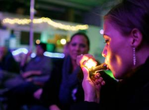 """FILE - In this Dec. 31, 2012 file photo, Rachel Schaefer, of Denver, smokes marijuana on the official opening night of Club 64, a marijuana-specific social club, where a New Year's Eve party was held in Denver. Denver is starting work on becoming the first city in the nation to allow marijuana clubs and public pot use in places like restaurants, yoga studios and art galleries. Voters narrowly approved the """"social use"""" measure last November. (AP Photo/Brennan Linsley, File)"""
