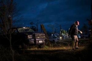 A member of the media walks near a truck that was damaged by an apparent tornado, Monday, Jan. 23, 2017, in Albany, Ga. A vast storm system kicked up apparent tornadoes, shredded mobile homes and left other destruction scattered around the Southeast over the weekend. (AP Photo/Branden Camp)