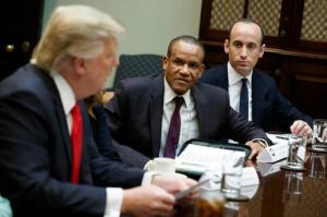 Stephen Miller, senior adviser to President Donald Trump, right, and Larry McKenney of Capitol Radiology listen as Trump speaks during a meeting with business leaders in the Roosevelt Room of the White House in Washington, Monday, Jan. 30, 2017. (AP Photo/Evan Vucci)
