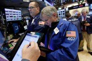 Richard Newman, center, works with fellow traders on the floor of the New York Stock Exchange, Wednesday, Jan. 25, 2017. The Dow Jones industrial average is trading over 20,000 points for the first time, the latest milestone in a record-setting drive for the stock market. The market has been marching steadily higher since bottoming out in March 2009 in the aftermath of the financial crisis. (AP Photo/Richard Drew)