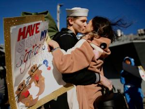 """In costume and carrying a sign reading, """"Have u seen my significant otter?"""" Melanie Till welcomes her husband, P.O. 3rd Class David Till, home after the USS Dwight D. Eisenhower returned to Naval Station Norfolk, in Norfolk, Va., on Friday, Dec, 30, 2016, from a seven-month deployment to the Middle East and the Mediterranean Sea. (Stephen M. Katz/The Virginian-Pilot via AP)"""