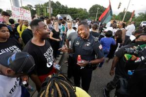 FILE - In this Aug. 15, 2016 file photo, Memphis police department Lieutenant A. Gardner, center right, talks with a protester, Antonio Blair, center left, during a protest at  Graceland's Elvis Candelight Vigil in Memphis, Tenn. Five people have filed a federal civil rights lawsuit against the city of Memphis and Elvis Presley's Graceland, saying they were discriminated against at a protest by a coalition associated with the Black Lives Matter movement during the annual vigil commemorating the singer's death. Graceland owner, Elvis Presley Enterprises, and the city are named in the complaint filed Wednesday, Jan. 18, 2017 in federal court. (Nikki Boertman/The Commercial Appeal via AP)