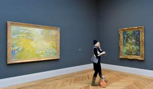 A journalist stands in a room with paintings by Claude Monet in the newly opened Barberini museum in Potsdam, eastern Germany, Thursday, Jan. 19, 2017. (Bernd Settnik/dpa via AP)