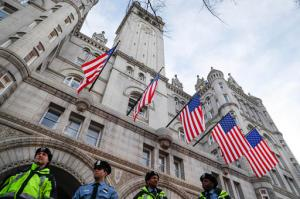 In this Jan. 19, 2017, photo, police stand guard outside the Trump International Hotel on Pennsylvania Avenue in Washington. While President Donald Trump's hotel in Washington did serve as a hub of inaugural activities it also stands as ground zero for what top Democrats and some ethics advisers see as his unique web of conflicts of interest. Trump's lease with the federal government to develop and operate a hotel inside the historic Old Post Office building expressly prohibits any elected official from benefiting from the property, yet Trump has not divested from his company or this particular project. (AP Photo/John Minchillo)