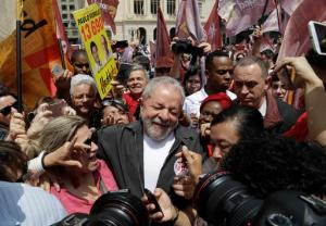 FILE - In this Sept. 30, 2016 file photo, Brazil's former President Luiz Inacio Lula da Silva is surrounded by supporters as he campaigns for Sao Paulo's Mayor Fernando Haddad, who's running for re-election with the Workers Party, in Sao Paulo, Brazil. The political return of Silva seems as inevitable to Brazilians as it is strange to outsiders. His time in office, from 2003 to 2010, coincided with Brazil's unprecedented boom, and he is revered by many for using those gains to pull millions out of poverty. Known to Brazilians simply as Lula, he is topping polls for the 2018 presidential race. (AP Photo/Andre Penner, File)