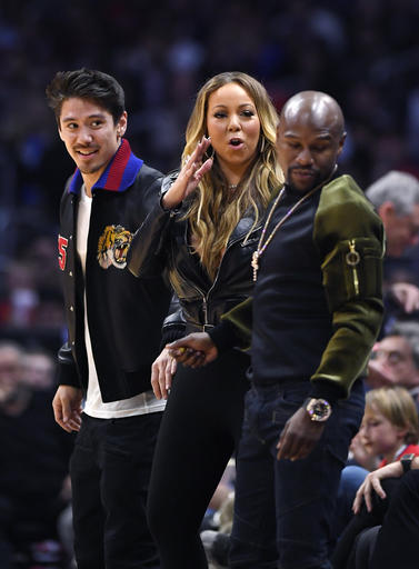 Singer Mariah Carey, center, talks with boxer Floyd Mayweather Jr., right, as Bryan Tanaka stands nearby during the second half of an NBA basketball game between the Atlanta Hawks and the Los Angeles Clippers on Wednesday, Feb. 15, 2017, in Los Angeles. The Clippers won 99-84. (AP Photo/Mark J. Terrill)