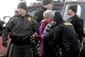 An elderly woman is escorted to a transport van after being arrested by law enforcement at the Oceti Sakowin camp as part of the final sweep of the Dakota Access pipeline protesters in Morton County, Thursday, Feb. 23, 2017, near Cannon Ball, N.D. (Mike McCleary/The Bismarck Tribune via AP, Pool)