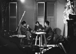 FILE - In this 1962 file photo provided by the Joe Alper Photo Collection LLC, Bob Dylan, left, his girlfriend Suze Rotollo center and Lena Spencer gather around a table at her coffeehouse, Caffe Lena in Saratoga Springs, N.Y. Dylan would surely still recognize the low-ceilinged room in Caffe Lena where he played a couple of gigs 60 years ago. But just about everything else about a venue that bills itself as the nation's oldest continuously operating coffeehouse has undergone some major upgrades as part of a $2 million renovation project bankrolled by some of folk music's biggest names. (Joe Alper Photo Collection LLC/Joe Alper via AP, File)