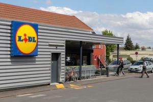 FILE - In this Thursday, June 16, 2011, file photo, people walk into a Lidl supermarket in Chambourcy, 30 kms (29 mls) west of Paris. Lidl, the German no-frills supermarket chain, is opening its first wave of stores in the U.S. summer 2017 ahead of schedule, announced Wednesday, Feb. 15, 2017. (AP Photo/Michel Euler, File)