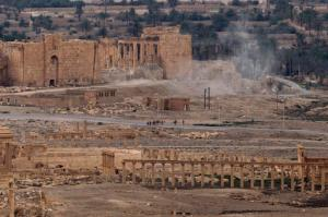 FILE -- In this April 14, 2016 file photo, Russian soldiers stand on a road as smoke rises from a controlled land mine detonation by Russian experts inside the ancient town of Palmyra, Syria in the central Homs province. Russia's defense ministry has released drone footage Monday, Feb. 13, 2017, showing new damage to Palmyra's archaeological site. The Islamic State group recaptured the ancient town in December from government troops, nine months after they were expelled in a Russia-backed offensive. The defense ministry said the footage was filmed earlier this month and showed a central section of Palmyra's famous theater lying in ruins. (AP Photo/Hassan Ammar, File)