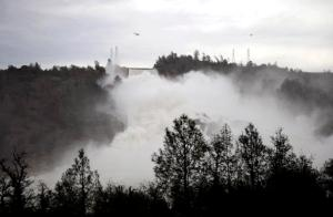 Water gushes down the Oroville Dam's main spillway Wednesday, Feb. 15, 2017, in Oroville, Calif. The Oroville Reservoir is continuing to drain Wednesday as state water officials scrambled to reduce the lake's level ahead of impending storms. (Chris Kaufman/The Appeal-Democrat via AP)
