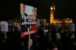 Demonstrators hold placards as they listen to speeches Monday Feb. 20, 2017, in London, during a rally in Parliament Square opposing U.S. President Donald Trump as MPs debate his planned state visit to the United Kingdom. (AP Photo/Tim Ireland)