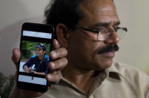 A man shows a picture of Alok Madasani, an engineer who was injured in the shooting Wednesday night in a crowded suburban Kansas City bar, on a mobile phone as Madasani's father Jaganmohan Reddy talks to the media at his residence in Hyderabad, India, Friday, Feb. 24, 2017. The shooting of two Indians in the crowded suburban Kansas City bar has sent shock waves through their hometowns, and India's government is rushing diplomats to monitor progress in investigation into the crime. The suspect, Adam Purinton, has been taken into custody and charged on Thursday with murder and attempted murder. (AP Photo/Mahesh Kumar A.)