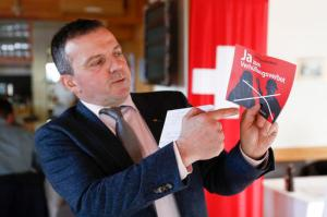 "National Councillor Walter Wobmann displays a leaflet reading ""Yes to the ban on veiling'' at the reunion of the Swiss People's Party SVP in Dornach, Switzerland, Sunday, Feb. 12, 2017. Swiss voters were deciding Sunday whether to make it easier for ""third-generation foreigners"" to get Swiss citizenship and whether to lock in competitive low tax rates for foreign companies in Switzerland. (Peter Klaunzer/Keystone via AP)"