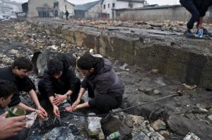 Afghan refugees wash themselves outside an abandoned warehouse where they and other migrants have taken refuge in Belgrade, Serbia, Wednesday, Feb. 1, 2017.  Hundreds of migrants have been sleeping rough in freezing conditions in central Belgrade looking for ways to cross the heavily guarded EU borders. (AP Photo/Muhammed Muheisen)
