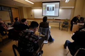 In this Friday, Jan. 20, 2017, photo, students in a journalism course at Kean University in Union, N.J., watch a presentation on fake news. Teachers from elementary school through college have been ramping up media literacy training to recognize bogus reports and understand their potential to weaken civic culture. (AP Photo/Julio Cortez)