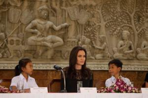 """Hollywood actress Angelina Jolie sits with child actress Sareum Srey Moch, left, and actor Mun Kimhak, right, during a press conference in Siem Reap, Cambodia, Saturday, Feb. 18, 2017. Jolie on Saturday launches her two-day film screening of """"First They Killed My Father"""" in the Angkor complex in Siem Reap province. (AP Photo/Heng Sinith)"""