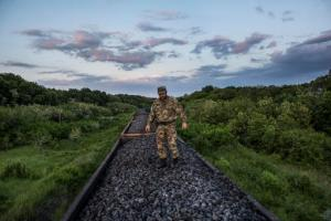 FILE - In this Tuesday, June 2, 2015 file photo, Mykola Tsukur, deputy commander of the volunteer Tornado battalion, stands atop a train carrying coking coal from the rebel-held parts of the Luhansk region into the government-controlled area in Orekhove, Ukraine. President Petro Poroshenko on Thursday, Feb. 16, 2017, has pledged to resume coal supplies from separatist-controlled parts of eastern Ukraine. (AP Photo/Evgeniy Maloletka, File)