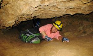 FILE - In this July 3, 2008, file photo, New Mexico Tech professor Penny Boston crawls through the Mud Turtle Passage on the way to the Snowy River formation during an expedition in Fort Stanton Cave, N.M. Boston, who discovered extreme life in New Mexico caves in 2008, presented new findings on Friday, Feb. 17, 2017 of microbes trapped in crystals in Mexico that could be 50,000 years old. (AP Photo/Susan Montoya Bryan)