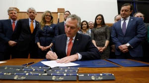 Virginia Gov. Terry McAuliffe, center, signs one of several bills relating to opioid addiction during a ceremony in the Patrick Henry Building in Richmond, Va., Thursday, Feb. 23, 2017. Looking on, from left, are Secretary of Public Safety and Homeland Security Brian J. Moran, Attorney General Mark Herring, Sen. Jennifer T. Wexton, D-Loudoun, Del. Dave A. LaRock, R-Loudoun, Del. Jennifer B. Boysko, D-Fairfax, Del. John M. O'Bannon III,, MD, R-Henrico, Ginny Atwood Lovitt, sister of heroin overdose victim Chris Atwood,, Del. Todd E. Pillion, R-Washington and others. (Bob Brown/Richmond Times-Dispatch via AP)