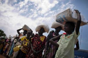 In this photo taken Wednesday, Oct. 19, 2016 and released by UNICEF, a young girl who fled fighting in nearby Leer in recent months, queues for food aid at a food distribution made by the World Food Programme in Bentiu, South Sudan. Famine has been declared Monday, Feb. 20, 2017 in two counties of South Sudan, according to an announcement by the South Sudan government and three U.N. agencies, which says the calamity is the result of prolonged civil war and an entrenched economic crisis that has devastated the war-torn East African nation. (Kate Holt/UNICEF via AP)