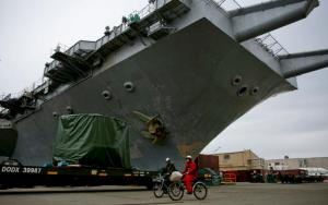 Following a decommissioning ceremony, two shipyard workers ride their bicycles by the the USS Enterprise aircraft carrier at Newport News Shipbuilding in Newport News, Va., on Friday, Feb. 3, 2017. It served more than 50 years, playing a role in the Cuban Missile Crisis, Vietnam and the wars in Iraq and Afghanistan. (Kristen Zeis/The Virginian-Pilot via AP)