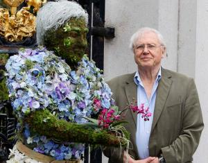 "FILE - In this Thursday, May 17, 2012 file photo, British television personality Sir David Attenborough stands with a floral sculpture of himself at Kew Gardens in London. From jungles to deserts to mountains, the BBC's epic nature series ""Planet Earth II"" takes viewers around the world - and around many genres of television. The seven-part series, which begins in the U.S. on Saturday, Feb. 18, 2017 with a simulcast on BBC America, AMC and SundanceTV, is a spectacular demonstration of how far nature programs have come. And no one has been more closely linked to their evolution than David Attenborough, the 90-year-old naturalist who narrates ""Planet Earth II."" (AP Photo/Kirsty Wigglesworth, File)"