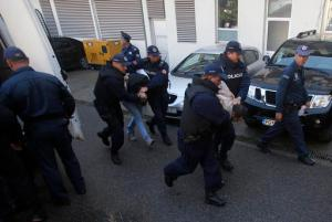 In this Sunday, Oct. 16, 2016 file photo, Montenegrin police officers escort people suspected of planning armed attacks after the parliamentary vote in Podgorica, Montenegro. Montenegro's special prosecutor  Milivoje Katnic, has accused Russia and its secret service operatives of plotting a coup attempt that included plans to kill the small Balkan country's former prime minister, Milo Djukanovic, following an investigation. (AP Photo/Darko Vojinovic, File)