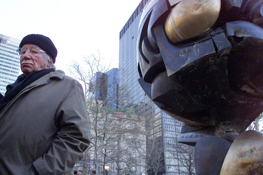 "FILE - In this file photo dated Monday, March 11, 2002, German artist Fritz Koenig stands next to his bronze sculpture ""The Sphere"" after a dedication ceremony in New York.  Koenig who's artwork ""The Sphere"" became a symbol of resilience after the 9/11 attacks in New York, died Wednesday Feb. 22, 2017 aged 92, according to news reports and Bavaria state's Ministry of Culture. (AP Photo/Beth A. Keiser, FILE)"