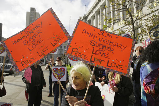 Ruth Wechsler waves a pair of signs in support of a Summer of Love anniversary concert during a protest outside City Hall Thursday, Feb. 16, 2017, in San Francisco. The show might still go on but a concert planned to mark the 50th anniversary of the Summer of Love has hit another major bureaucratic hurdle. San Francisco's Recreation and Park Commission on Thursday upheld its decision earlier this month to deny a permit for the concert. (AP Photo/Eric Risberg)