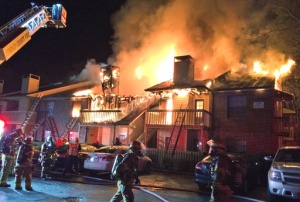This image provided by the Henrico County Division of Fire shows firefighters responding to a suburban Richmond apartment complex fire early Friday morning March, 3, 2017 in Henrico, Va. The fire department said that 20 adults and one child were displaced and it appears 12 apartments will be uninhabitable in the 1:45am blaze that was brought under control in about 90 minutes. (Henrico County Division of Fire via AP)