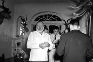 FILE - In this Oct. 28, 1954 file photo, American novelist Ernest Hemingway meets the press at his Cuban home in San Francisco de Paula, a suburb of Havana, after the announcement was made that he is awarded the 1954 Nobel Prize in literature. The reporter seen at rear center is Sam Summerlin of the Associated Press. Associated Press foreign correspondent Summerlin, who flashed the news to the world that the Korean War had ended and who reported on everything from Latin American revolutions to U.S. race riots during a long and distinguished career, has died at age 89. He died Monday, Feb. 27, 2017, at a care home in Carlsbad, Calif., from complications of Parkinson's disease, according to his daughter, Claire Slattery of Encinitas, Calif.  (AP Photo, File)