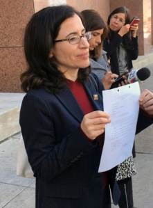 Dallas immigration attorney Fatma Marouf holds up a bond order in front of the federal building after leaving immigration court in Dallas, Thursday, March 2, 2017, from a federal immigration judge for Sara Beltran Hernandez, a Salvadoran woman seeking asylum. An immigration judge has granted bond to Hernandez so she can leave a detention facility to seek treatment for a brain tumor. (AP Photo/Claudia Lauer)
