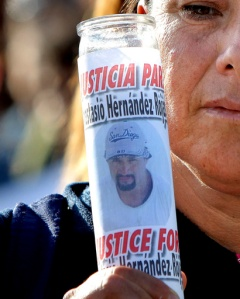 FILE - In this June 3, 2010 file photo, a woman holds a votive candle with an image of Anastasio Hernandez during a protest at the San Ysidro border crossing that separates Tijuana from San Diego, in Tijuana, Mexico. A federal judge tentatively approved an agreement Thursday, March 2, 2017, for the U.S. government to pay $1 million to the children of Hernandez, who died after being detained by immigration authorities and shot several times with a stun gun in 2010. The settlement is intended to end a nearly 7-year case that prompted widespread complaints that U.S. immigration authorities tolerated agents who use excessive force. (AP Photo, File)